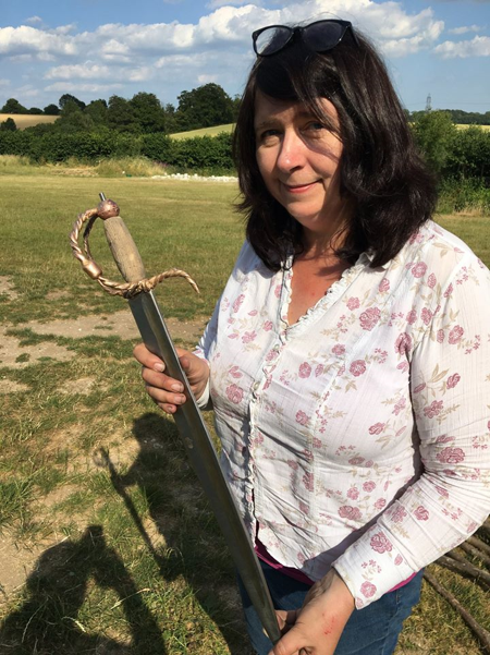Picture of Helen Steadman holding the sword she has made. She's wearing a white shirt with pink roses on and jeans. Her fingernails are filthy and there are small cuts all over her hands.
